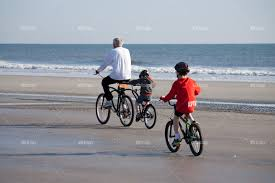 Father And Sons Riding Bikes On The Beach
