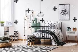 hocker auf geometrischem teppich und grüner decke auf bett im jugendzimmer mit kaktusmotiv
