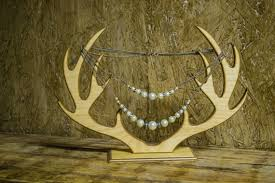 Creative Jewelry Display Using Antlers On A Wood Background