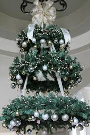 A Chandelier Made Of Faux Evergreen Wreaths And Silver Gold Ornaments