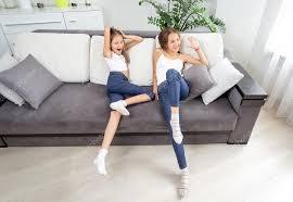 zwei mädchen haben spaß auf dem sofa im wohnzimmer