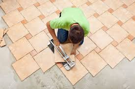 Man Laying Ceramic Floor Tiles Working With A Cutter Device