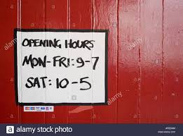 opening hours found on abandoned warehouse door stock photo