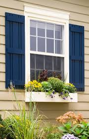 Dark Blue Shutters On A Beige House Flank Window With Decorative Outdoor You Can Make Yourself And Paint For Maximum Impact