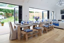Long Dining Table In Open Plan Living Area With Bifold Doors Looking Out Onto The Garden