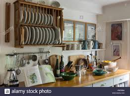 Rustic Style Kitchen With Wooden Plate Rack Assorted Jugs And Work Top