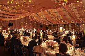 Guests Sitting At Reception Tables With Drapes Overhead