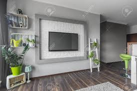 wohnzimmer mit dem großen fernsehapparat der an einer dekorativen wand mit weißem ziegelsteineffekt hängt