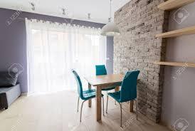 moderne esszimmer mit alten grauen ziegelmauer holztisch türkisfarbenen ledersesseln und leeren regalen grau scheinwerfer an der decke