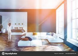 frau wohnzimmer mit blauen wänden holzboden großen fenstern