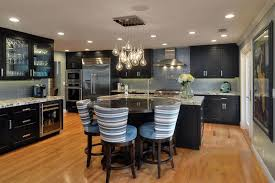 Contemporary Kitchen With Dark Cabinetry White Quartz Counter Porcelain Tile Backsplash Light Wood