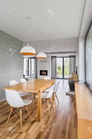 esszimmer mit holztisch weißen stühlen und modernen len