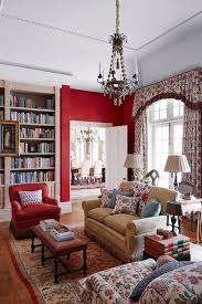 A Red Colour Scheme In Living Room Cum Library With White Bookcase Floral Curtains