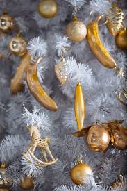 Golden Christmas Toys Hanging On White Artificial Tree By Pietro Karras For Stocksy United
