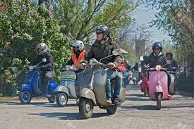 A Group Of Bikers Riding Vintage Italian Scooters Lambretta And Vespa At Motorcycle Rally