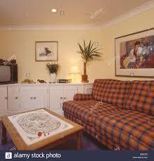 orange und blau aufgegebenes sofa in pastell gelb wohnzimmer