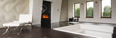 geräumiges stilvolles wohnzimmer mit weißem sofa und modernem kamin