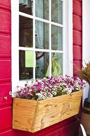 An Unfinished Wooden Window Box On The Side Of A Barn Red Building Is Filled