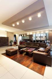 Beige Tile Flooring Surrounds A Small Wooden Section That Houses The Leather Sectional Of Living