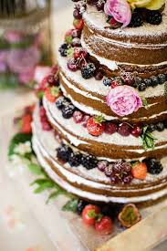 Naked Wedding Cake With Each Layer Covered In Berries And Dusted Icing Sugar
