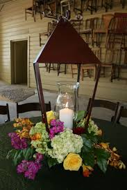 Brown Traditional Iron Lantern Combined With Cylinder Glass Candleholder Along Beautiful Flowers