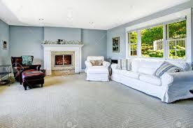 hellblau wohnzimmer mit weißen sofa sessel und ledersessel und gemütlichem kamin