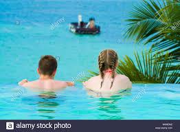 100 Infinity Swimming Caucasian Teenagers Relaxing In Infinity Swimming Pool In Luxury