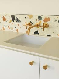 White Terrazzo With Large Colored Inserts As A Backsplash For Kitchen