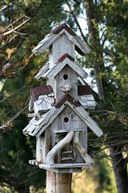 Rustic Three Story Drift Wood Bird House Perched On A Wooden Post