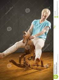 Young Blonde Woman Riding Wooden Rocking Horse In The Studio ...