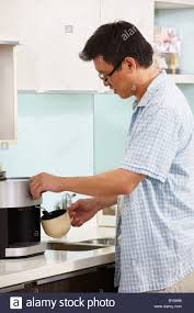 Asian Male Making Coffee At Kitchen In The Morning