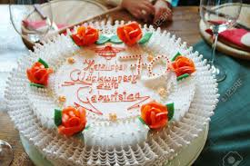 a fancy white cake with red roses for the happy birthday Stock
