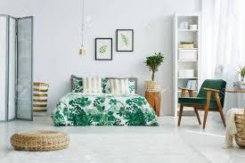 weißes schlafzimmer mit bildschirm bett sessel bücherregal le und hocker