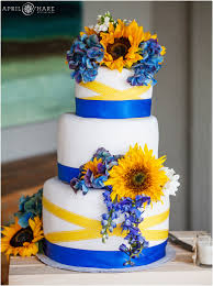 Three tiered blue and yellow white wedding cake with sunflowers at a pretty Colorado mountain wedding