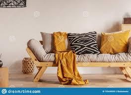 skandinavisches sofa mit kissen und dunkler gelber decke im