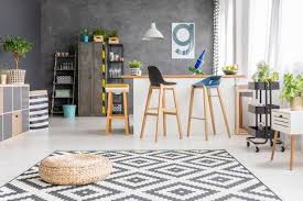 Pouf On Geometric Carpet In Spacious Dining Room With Bar Stools At Kitchen Island Against Concrete