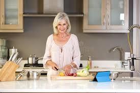 femmes plus cuisine une femme plus âgée dans des légumes de coupe de cuisine image stock