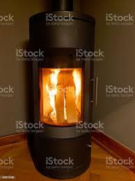 eine moderne brennende schwarz eisernen ofen mit schornstein ist im wohnzimmer in einer ecke stockfoto und mehr bilder beleuchtet