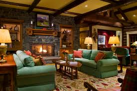 Great Fabric Green Sofas And Cushions As Well Log Wood Coffee Table Also Stacked Stone Fireplace Panel In Rustic Living Room Decors