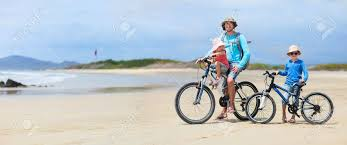 Father And Kids Riding Bikes Along A Beach Stock Photo