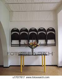 schwarz faltende stühle gelagert auf wand unterhalb