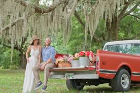 Bride And Groom Sitting On Red Vintage Truck
