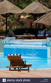 A Wooden Sun Lounger Next To Swimming Pool In Luxury Holiday Resort