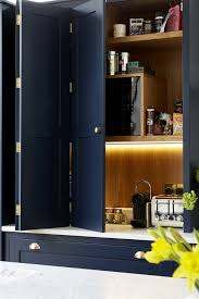 The Cabinets Hold Appliances And Are Lit Up Inside For Comfort