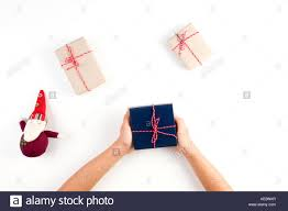 Top View Of Kid Hands Holding A Present Gift Boxes Packed In Craft Paper And Christmas Decoration On White Table