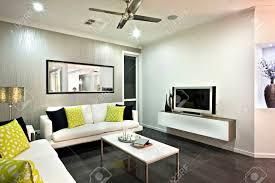 wohnzimmer mit einem spiegel und fernseher unter dem ventilator an der decke schließen gibt es ein sofa mit kissen in der nähe der kleinen tisch auf