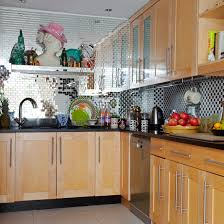Small Kitchen With Mirrored Splashback Tiles Wooden Cabinetry And Dark Worktops