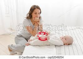 pensive mutter mit baby im schlafzimmer junge frau die mit