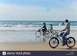 Family Riding Bikes On Beach San Diego California
