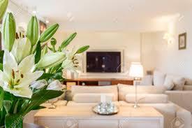 frische blumen auf dem tisch in einem geräumigen hellen wohnzimmer mit sofa und fernseher